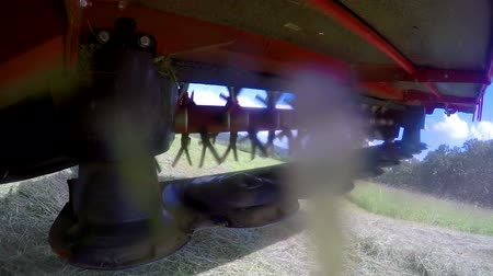 keser : Rotary rakes are turning a dry cut grass around. A farmer is driving a tractor across the field. Close-up shot.