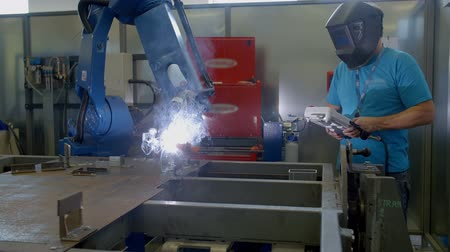 automatizálás : A worker in the factory is regulating a robotic drilling system with a small device. Sparks are flying all around. A man is wearing a welding helmet.