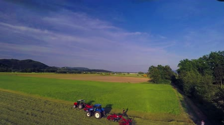 еще : Three tractors are busy raking hay on a hot summer day. The meadow looks huge yet beautiful. The nature is outstanding. Wide-angle aerial shot.
