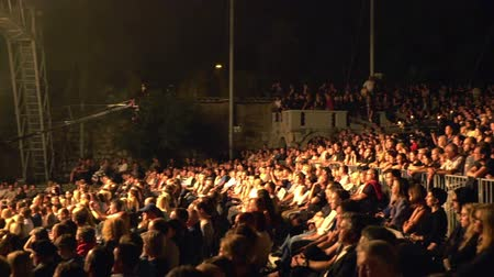 musicians stage : A big crowd of people of all generations has come to listen to Laibachs concert at Križanke Outdoor Theatre. Wide-angle shot. Stock Footage