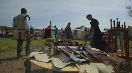 rytíř : SENTRUPERT FESTIVAL SEPTEMBER 2016 There are many weapons displayed on tables at a medieval festival. There is also a cowhide rug on a table and a few tents of different colours in the background. Wide-angle shot. Dostupné videozáznamy