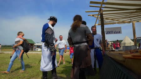 rytíř : SENTRUPERT FESTIVAL SEPTEMBER 2016 A few knights who are dressed in blue-and-white uniforms are standing by one of the stands and they are talking to each other. Close-up shot. Visitors are passing by.