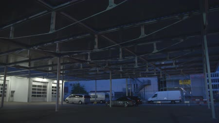 architectural protection : Lights on the roof of the parking lot are turned on. There are only a few cars parked over there. Wide-angle shot. Stock Footage