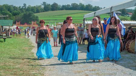 lovagi torna : A few belly dancers are walking down a path and they are wearing beautiful long blue dresses. It is a gorgeous summer day.