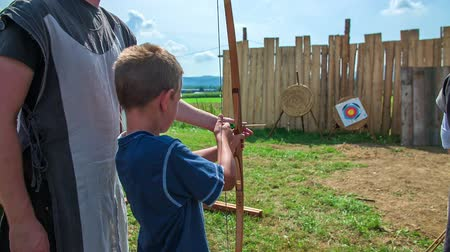 rytíř : A young boy doesnt know really how to hold a bow and an arrow. An adult is teaching him.