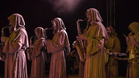 rytíř : The music band is having their hoodies on and they are playing their saxophones. It is evening time and they are performing for the audience. Dostupné videozáznamy