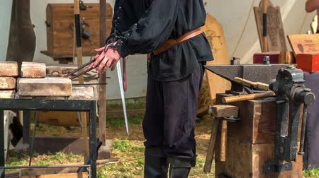 rytíř : A blacksmith is working in his workshop at a medieval festival. He is holding pliers in his hand and he wants to lift up an item with them. Dostupné videozáznamy