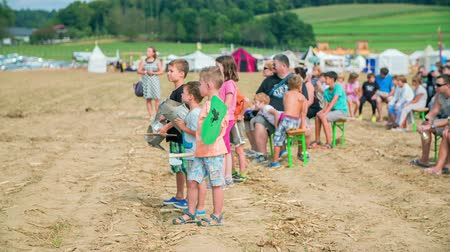 děje : Children are standing in the middle of the field and are watching the performance that is happening on stage. Their parents are sitting on benches behind them.