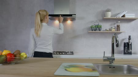 wipe off : A young woman is trying out different buttons on the kitchen ventilation. At the end, she turns everything off and leaves. Stock Footage