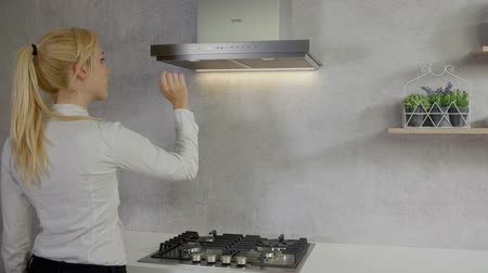 unplug : A young woman is coming to the kitchen and she is pressing a few buttons on the kitchen hood. Stock Footage