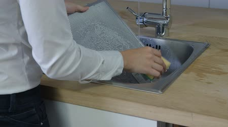 unplug : A young woman is thoroughly washing the filter from the kitchen ventilation and she is using some water and a sponge.