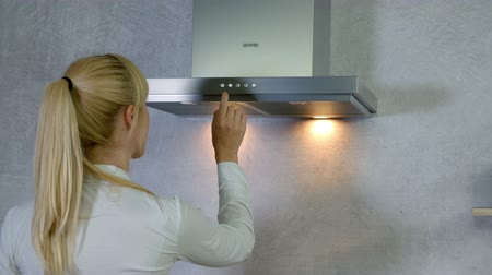 unplug : A young woman comes to the kitchen vent. She turns on a button and the lights turn on. Then she is pressing a few different buttons and then at the end, the lights turn off.