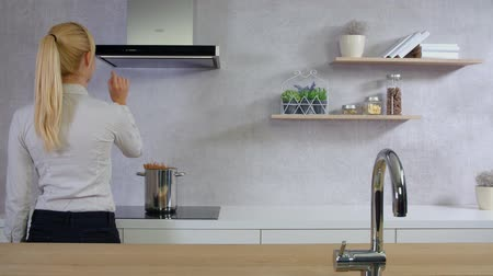 unplug : A young woman is coming into the kitchen and she is pressing on button on the kitchen hood. Stock Footage