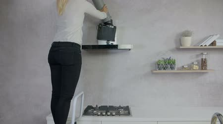 unplug : A young woman is standing on a bar stool and she is adjusting the kitchen hood and setting everything up.