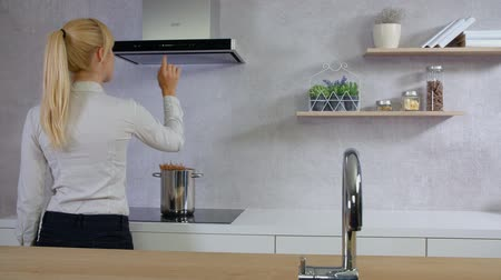 wipe off : A young woman is standing in front of a kitchen hood in the kitchen and she is carefully pressing a few buttons on the device.