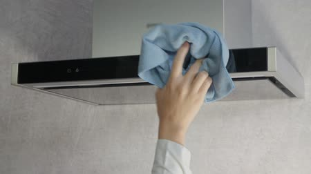 unplug : A young woman is wiping the surface of the kitchen ventilation with a blue cloth.