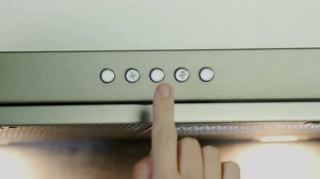 unplug : A young woman is playing with the buttons on a kitchen vent. She is trying all of them and then she turns the device off.