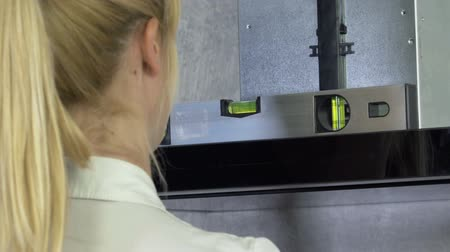 wipe off : A kitchen ventilation is askew and a young woman with blond hair is putting a meter on it to adjust the level so that it would be even. Stock Footage