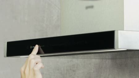 unplug : A young woman is turning on a kitchen hood and then she is adjusting the light on the device. Stock Footage