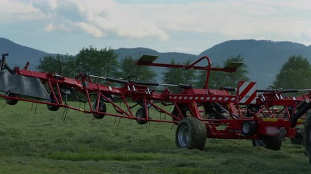 levantado : A red agricultural machinery is being lifted up. A farmer has finished working on the field and now, he is leaving the grass fields.