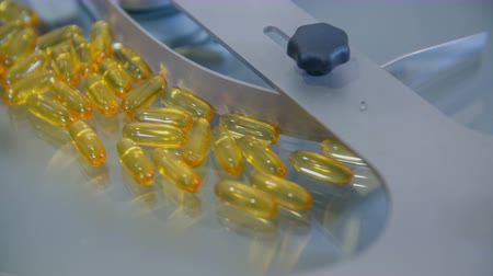 vitamin : Yellow pills are travelling on a conveyor belt and are spinning around in a circle. They will be sorted out into transparent cups.