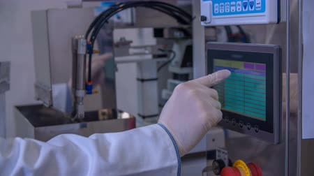 üretim : A pharmaceutical worker is touching a few buttons on the screen when controlling the whole production process. He is also wearing protective gloves and a gown.