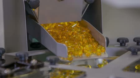 vitamin : Yellow pills are massively falling down on a conveyor belt and they will be sorted out into small transparent cups.