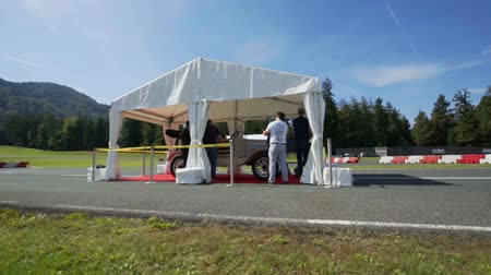 lüktet : We can see a few people under a tent and they are preparing something. It is a beautiful summer day in a sfae driving center.