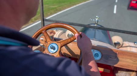 lüktet : We can see that a man in a convertible vintage wooden car is passing another vehicle on a track.