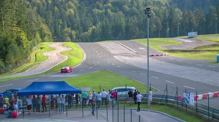 lüktet : A red car is racing on a track in a safe driving center. It disappears. Lots of people are watching it.