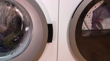 vending machine : Laundry and clothes are spinning in the washer and dryer. Machines are placed together in tidy utility room.