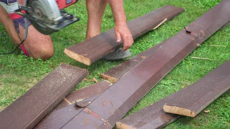 kőműves : Elderly man wearing shorts cutting dark brown wooden boards up into stripes wit a help of a handy circular saw. Stock mozgókép
