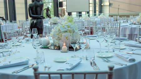 wed : Amazing scene ready for a wedding celebration. Round tables are all decorated in white with beautiful and fancy white bouquets.