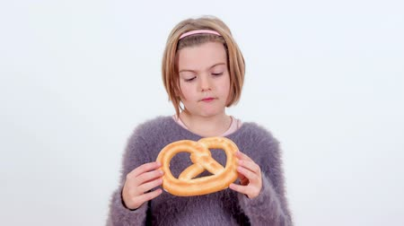 pretzel : A young girl is looking at a pretzel and then she is biting into it.