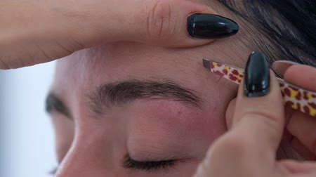 plucks : Shaping eyebrows. A make up artist plucks the clients eyebrows with tweezers. Stock Footage