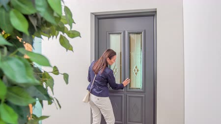 kapalı : A woman who is shopping for new door is approaching one of them, she touches the exterior and then she walks inside.