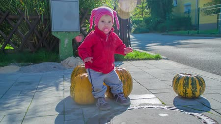 полый : A small girl is sitting on a pumpkin and she is happy. Its Halloween time. Стоковые видеозаписи