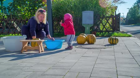 полый : A small toddler is spending some time abroad with her mom. She is cleaning the pumpkins as its Halloween time.