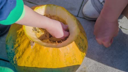 полый : A small boy is cleaning the pumpkin. He and his mom are going to decorate the house as its Halloween time. Стоковые видеозаписи