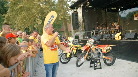 çok güzel : A singer is singing and he is in a very good mood. He is entertaining the crowd at a motocross racing event.