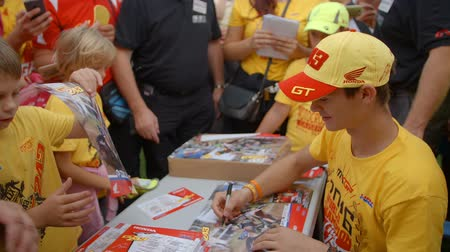 entusiasmo : A young star of the motorcross racing is signing posters for the children. They are all very happy because he is taking time and signing them for them.