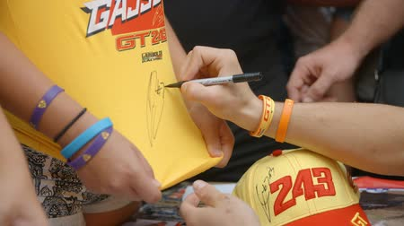 házigazda : A main motorcross racer is signing a T-shirt. Lots of children and other visitors would like to have his signature.