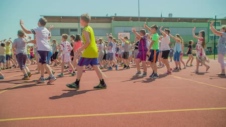 antrenör : GRIZE, SLOVENIA - 10. JUNE 2017  Small kids are standing on the sport facility outside the school and are waving at someone. Its summer time and they are spending time outdoors during their PE. Stok Video