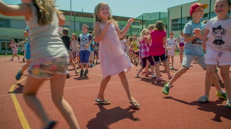 işe : GRIZE, SLOVENIA - 10. JUNE 2017  Children are playing catch me if you can on the sport facility. Its summer time. Theyre having fun spending time outdoors.