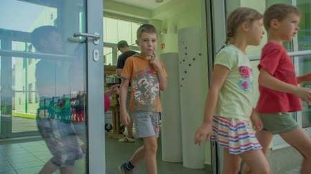 işe : GRIZE, SLOVENIA - 10. JUNE 2017  Children are walking outside the school door one by one. They are all dressed in summer clothes. One of the boys is also wearing sunglasses.