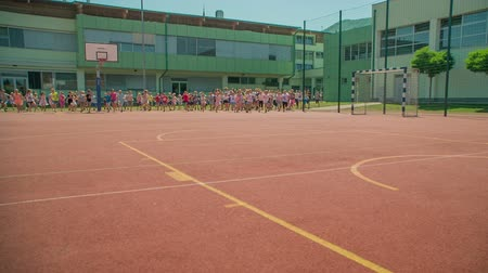 você : GRIZE, SLOVENIA - 10. JUNE 2017  Everyone is running from one side of the sport facility to the other. Its summer time and kids are happy playing outside.
