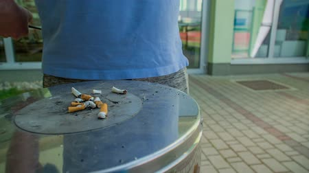 can : GRIZE, SLOVENIA - 10. JUNE 2017  There are lots of cigarette butts on the cigarette bin outside the school. Stock Footage