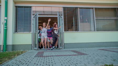 işe : GRIZE, SLOVENIA - 10. JUNE 2017  Children open the door and they lift their hands up when they start summer holidays. They are happy and joyful.