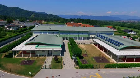 stadyum : GRIZE, SLOVENIA - 10. JUNE 2017  There is a narrow path which is leading to the entrance of the school. Aerial shot. Its summer time. Stok Video