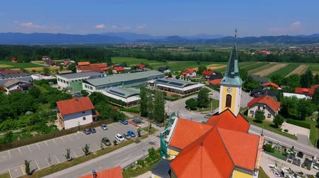 işe : GRIZE, SLOVENIA - 10. JUNE 2017  There is a yellow church and different houses in the village. We can see a beautiful landscape in the background.